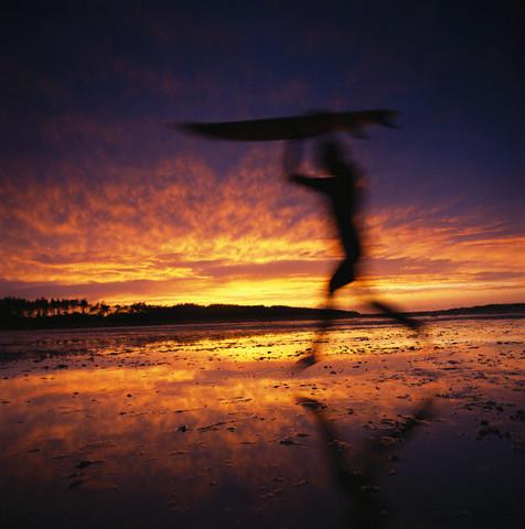 Surfer Running on Beach at Sunset